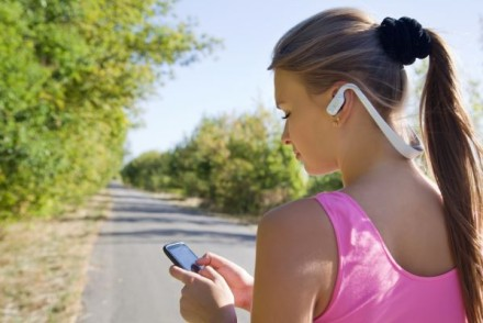 Girl with bluetooth wireless headphones for running